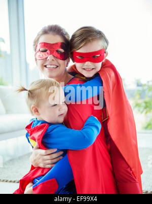 Superhero mother and children hugging in living room - Stock Photo