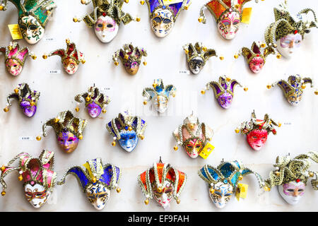 Colorful souvenir carnival masks with magnets displayed for sale on stand in Venice, Italy. - Stock Photo