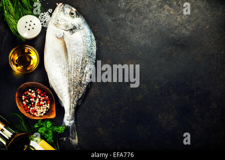 Delicious fresh fish on dark vintage background. Fish with aromatic herbs, spices and vegetables - healthy food, - Stock Photo