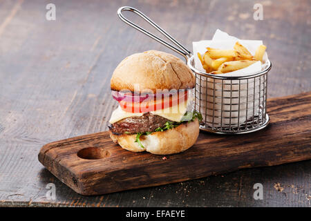 Burger with meat and French fries in basket on wooden background - Stock Photo
