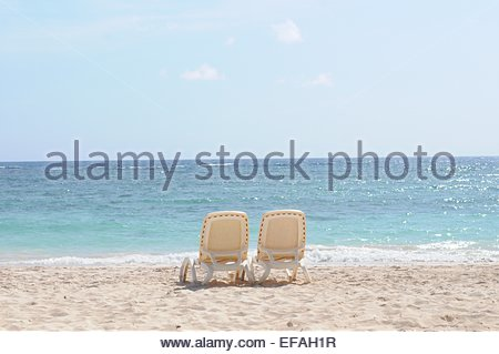 Two empty deck chairs on beach - Stockfoto