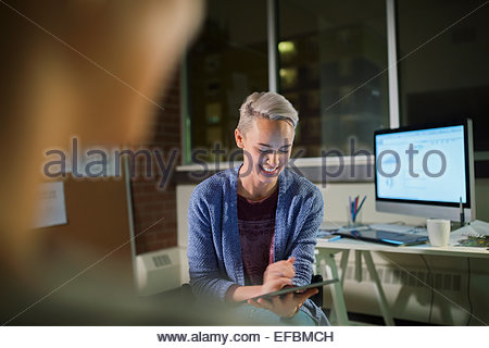 Businesswoman with digital tablet working late in office - Stock Photo