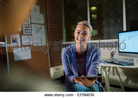 Businesswoman with digital tablet working late in office - Stockfoto
