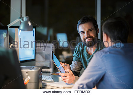 Businessmen with digital tablet working late in office - Stock Photo