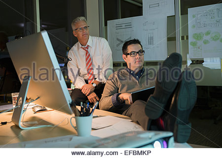 Businessmen working late in office - Stock Photo