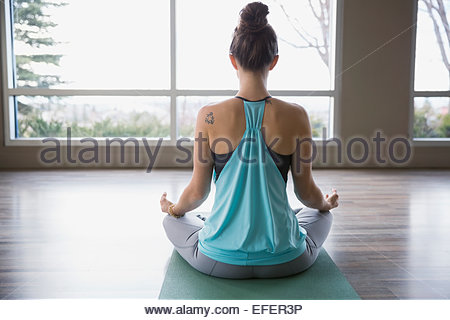 Rear view of woman meditating in lotus position - Stock Photo