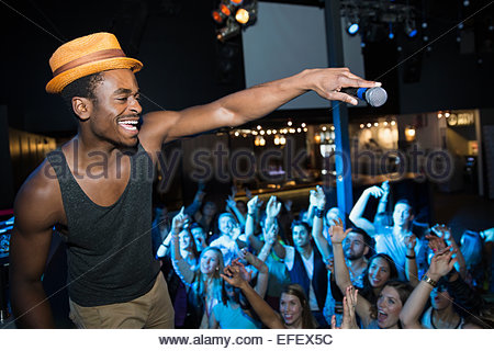 DJ with microphone above cheering nightclub crowd - Stock Photo