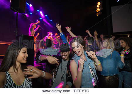 Friends dancing at music concert - Stock Photo