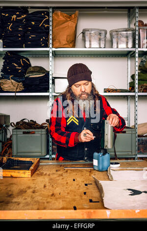 Mature worker filling up remaining ink in bottle from squeegee at worktable - Stock Photo