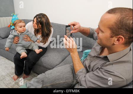 Father taking picture of mother and son at home - Stock Photo