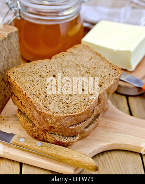Rye homemade bread with honey and butter on board - Stock Photo