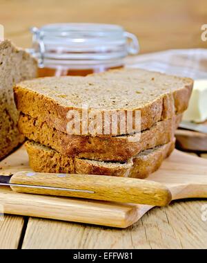 Hausgemachtes Roggenbrot mit Honig und Messer an Bord - Stockfoto