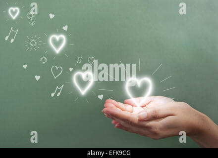Hands holding a glowing heart over a chalkboard copyspace - Stockfoto