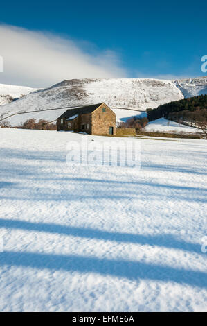A stone barn in a snowy winter landscape in the vale of Edale, Peak District, Derbyshire. Shadows on the snow. - Stock Photo
