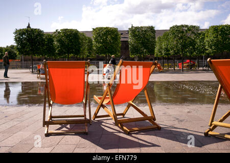 Granary Square King's Cross London summer deck chairs - Stock Photo