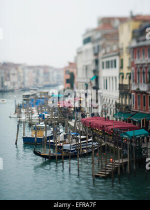 Wide canal in Venice, with boats and traditional gondolas moored along the waterfront, and restaurants and cafes. - Stock Photo
