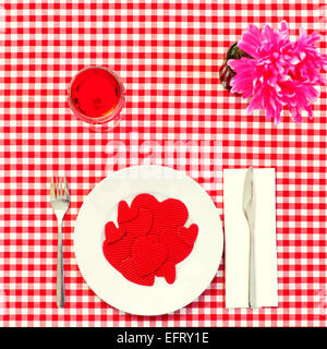 high-angle shot of a plate full of red hearts with different size on a set table with a checkered red and white - Stock Photo
