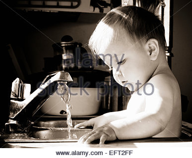 Portrait Of A Baby Boy Playing Playing With Water Bathing Bathtub Bath Kitchen Sink Thinking MR - Stock Photo