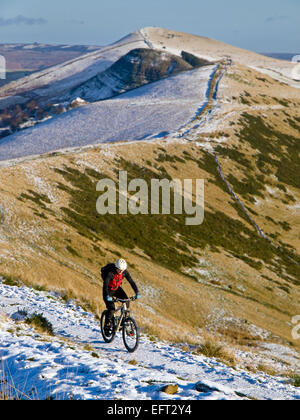 A mountain biker on The 'Great Ridge' between Mam Tor and Lose Hill in the Peak District National Park in winter - Stock Photo