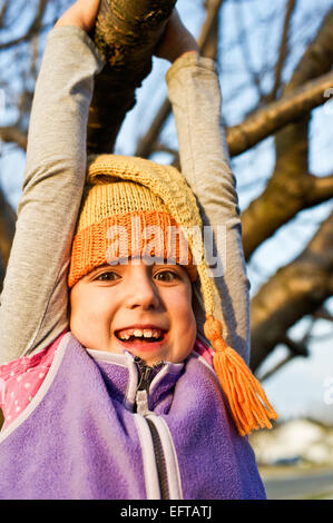 Young girl swinging on a tree branch in the autumn wearing knitted stocking cap. - Stock Photo