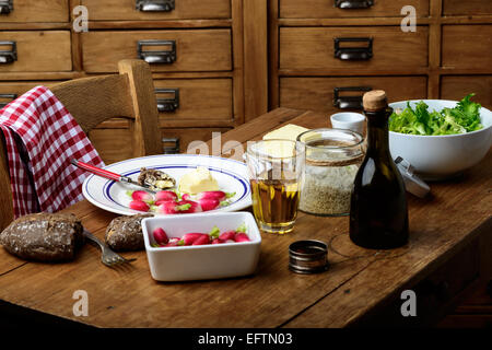 plate with radish, butter and salad on a table - Stock Photo