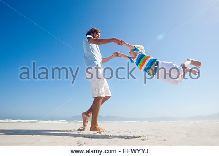 Smiling Father swinging son around playfully on sunny beach - Stock Photo