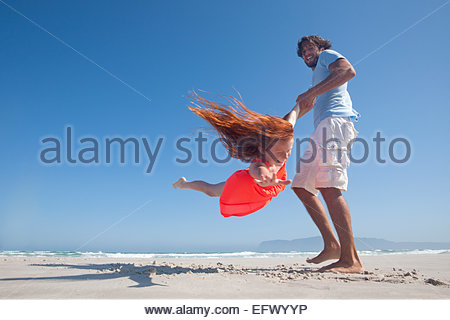 Smiling Father swinging daughter around playfully on sunny beach - Stock Photo