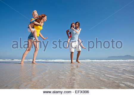 Mother and father, giving two children piggy back, whilst paddling in sea on sunny beach - Stock Photo