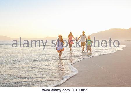 Happy family holding hands on sunny beach - Stock Photo