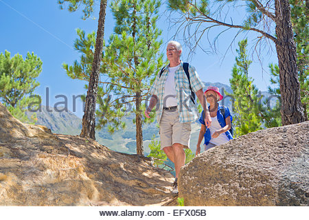 Senior couple hiking on mountain path - Stock Photo