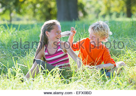 Young boy tickling young girl with feather, sitting in treelined field - Stockfoto