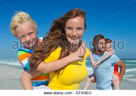 Mother and father, giving two children piggy back, on sunny beach - Stock Photo