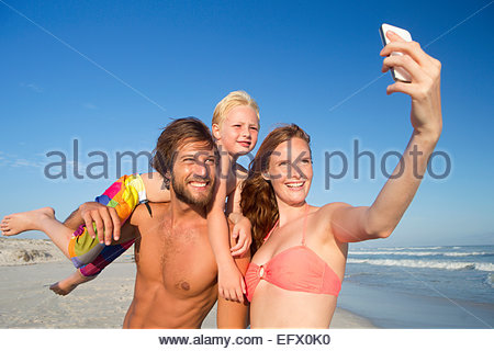 Portrait of happy couple with son on shoulder, taking selfie on sunny beach - Stockfoto