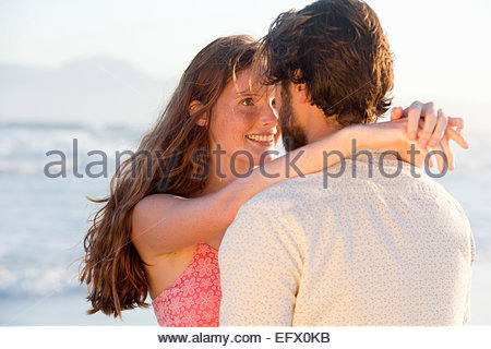 Romantic couple embracing, about to kiss, on sunny beach - Stock Photo