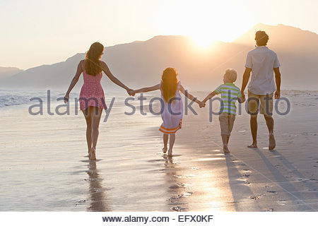 Happy family walking into distance, holding hands, on sunny beach - Stock Photo