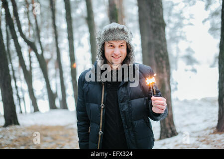 Groom holding Benghal light in snow-covered winter forest - Stock Photo