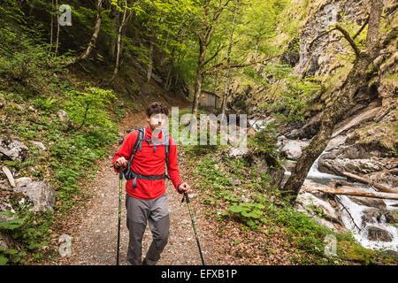 Young man hiking on river path, Oberstdorf, Bavaria, Germany - Stock Photo