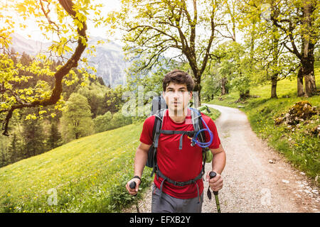 Young man hiking up rural road, Oberstdorf, Bavaria, Germany - Stock Photo