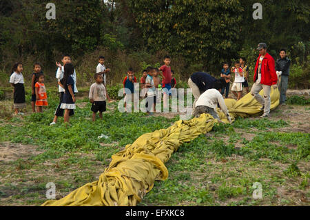 Horizontal view of young Laotian children helping to pack away a hot air balloon landed close to their village. - Stock Photo