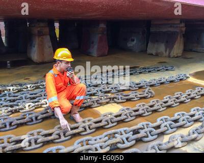 Dock worker in a shipyard talking on a walkie talkie - Stock Photo