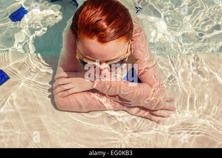 Young boy (6-7) wearing goggles, resting in swimming pool - Stock Photo