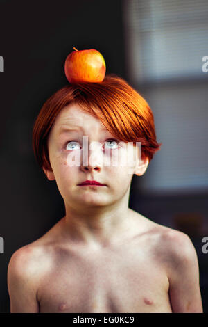 Boy balancing an apple on his head - Stock Photo