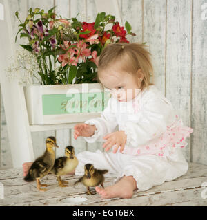 Portrait of a girl with Down syndrome with ducklings - Stock Photo
