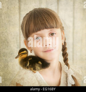 portrait of girl with duckling on shoulder - Stock Photo