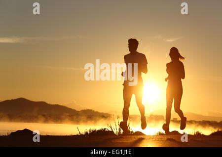 Silhouette of a couple running at sunset with the sun in the background - Stock Photo