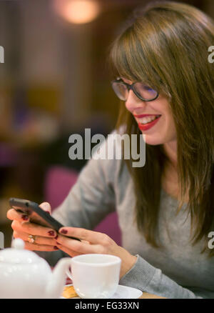 Beautiful young woman checking her mobile phone whilst having a hot drink a cosy cafe. - Stock Photo