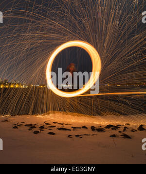 A man spinning wool outside at night with copyspace at the bottom - Stock Photo