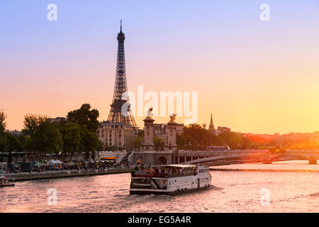 Paris, Tour boat on the Seine river at Sunset - Stock Photo