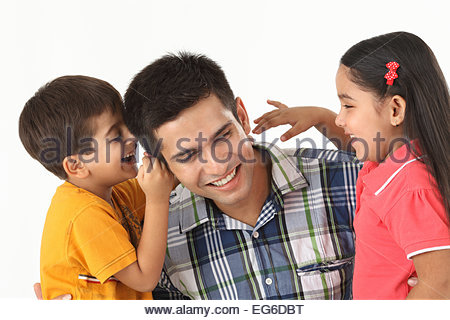 Close up of an Indian father with his two children smiling - Stockfoto