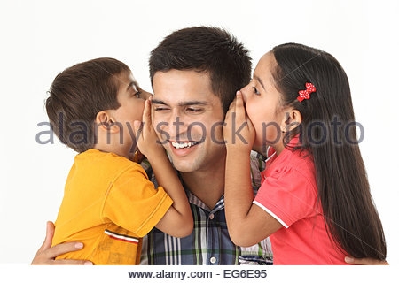 Indian boy and girl whispering into their father's ear - Stockfoto
